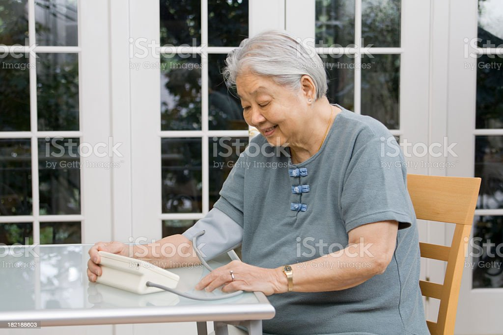 Senior Asian Woman Monitoring Her Blood Pressure Health at Home stock photo