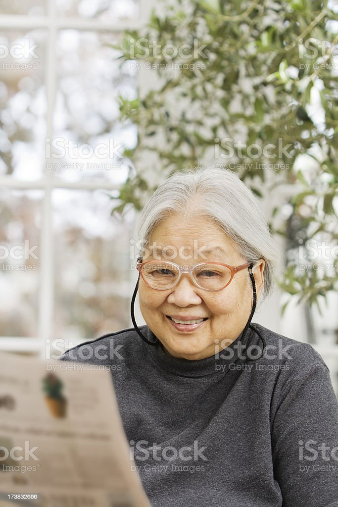 Senior Asian Woman Relaxing with Newspaper royalty-free stock photo