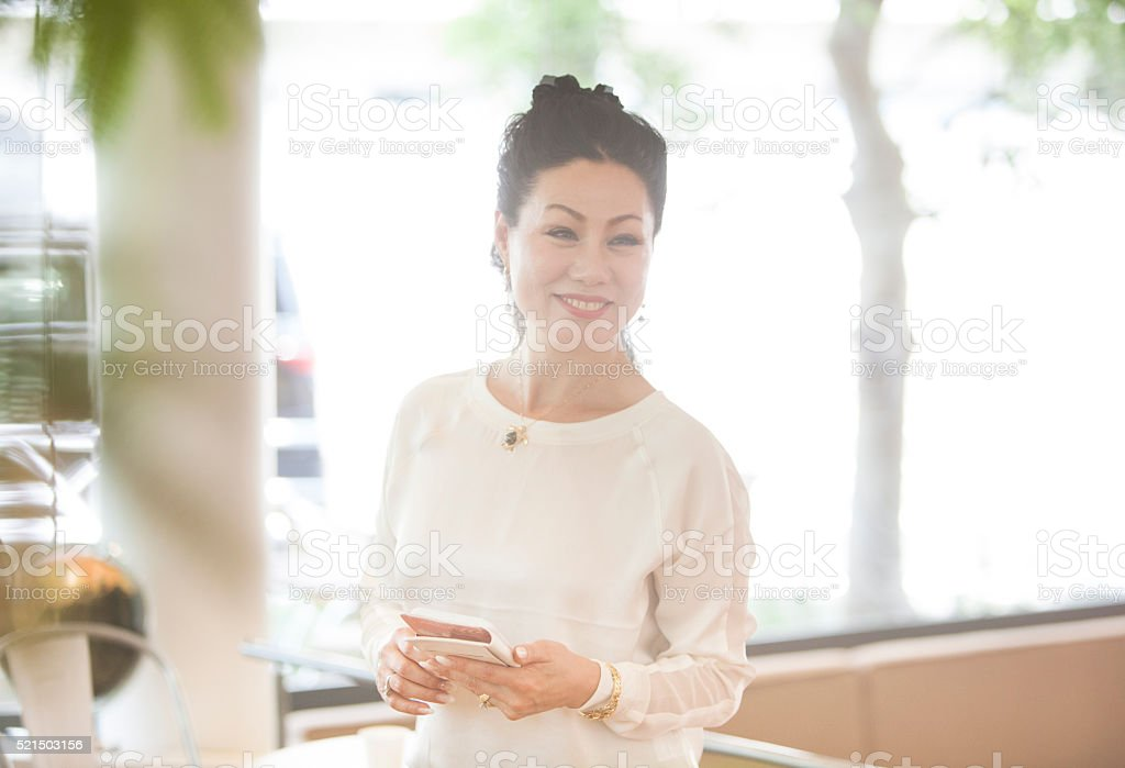 Senior Asian Woman Thanks The Staff With A Smile stock photo