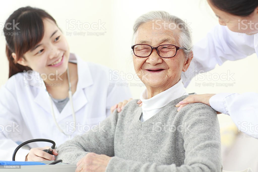 senior asian woman with doctor indoor royalty-free stock photo