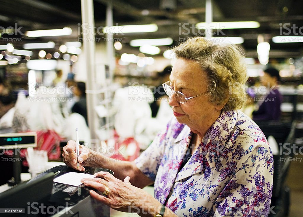 Senior at supermarket checkout royalty-free stock photo