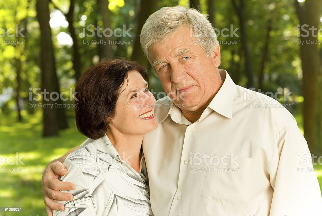 Senior attractive happy couple embracing in park royalty-free stock photo