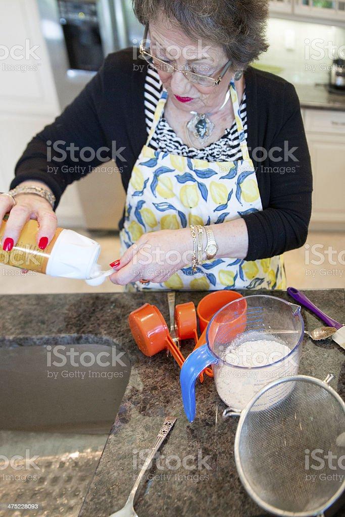 Senior Baking series-adding the dry ingredients royalty-free stock photo
