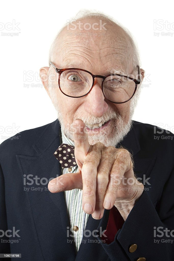 A senior bespectacled man points at the camera and winks stock photo