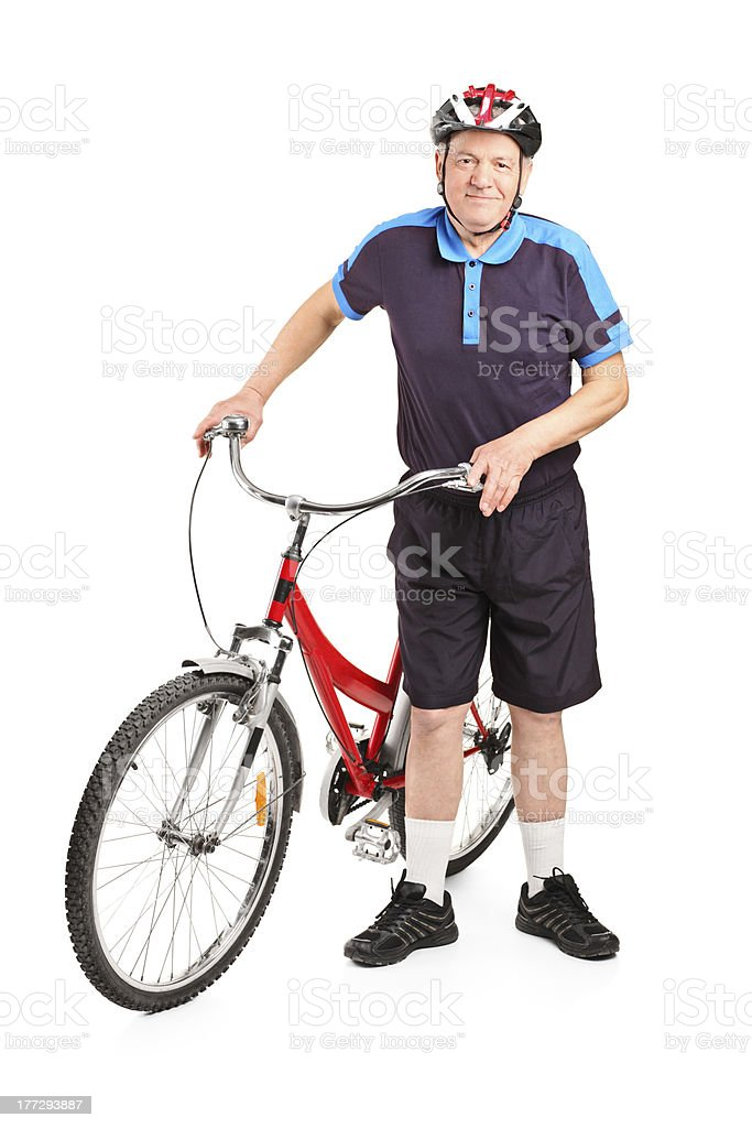 Senior bicyclist posing next to a bicycle royalty-free stock photo