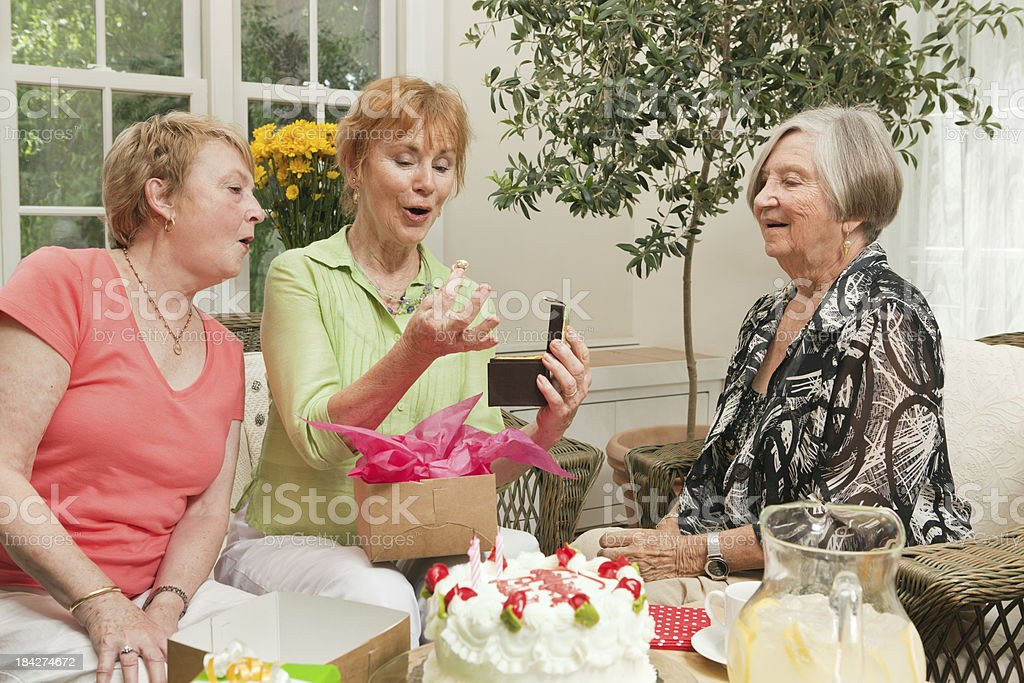 Senior Birthday Celebration with Cake and Presents Among Friends royalty-free stock photo
