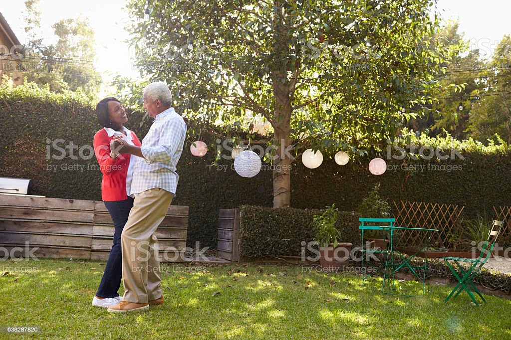 Senior black couple dance in their back garden, full length stock photo