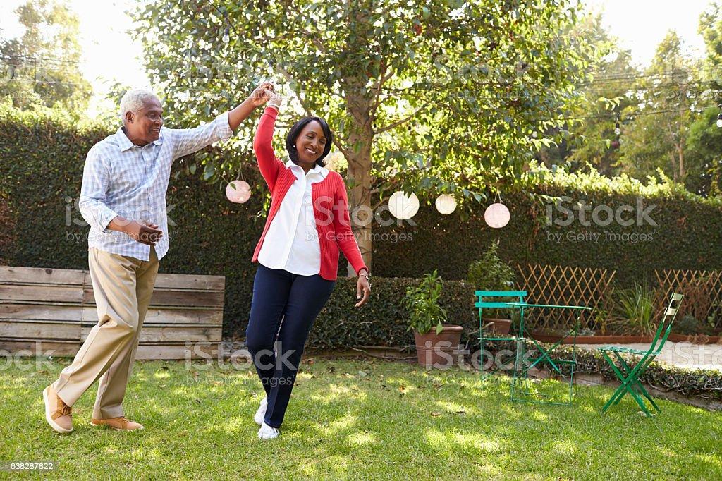 Senior black couple dance in their back garden, full length royalty-free stock photo