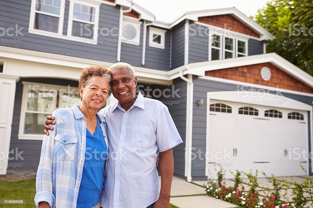 Senior black couple standing outside a large suburban house stock photo