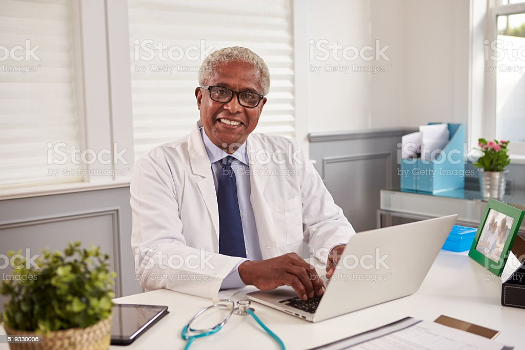 Senior black male doctor at an office desk looking stock photo