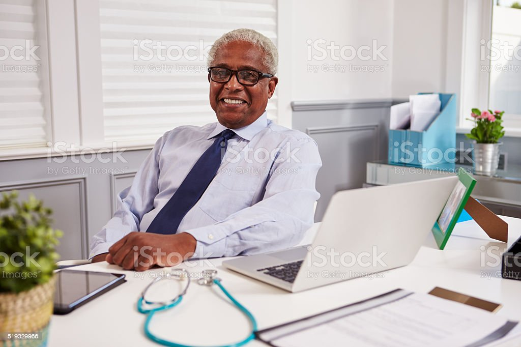 Senior black male doctor in an office looking to camera stock photo