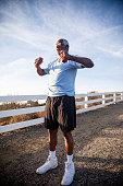 Senior Black Man Exercising Outdoors with Dumbells