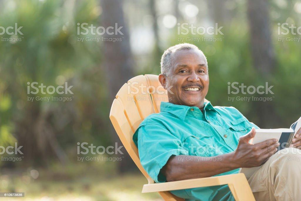 Senior black man reading book outdoors stock photo