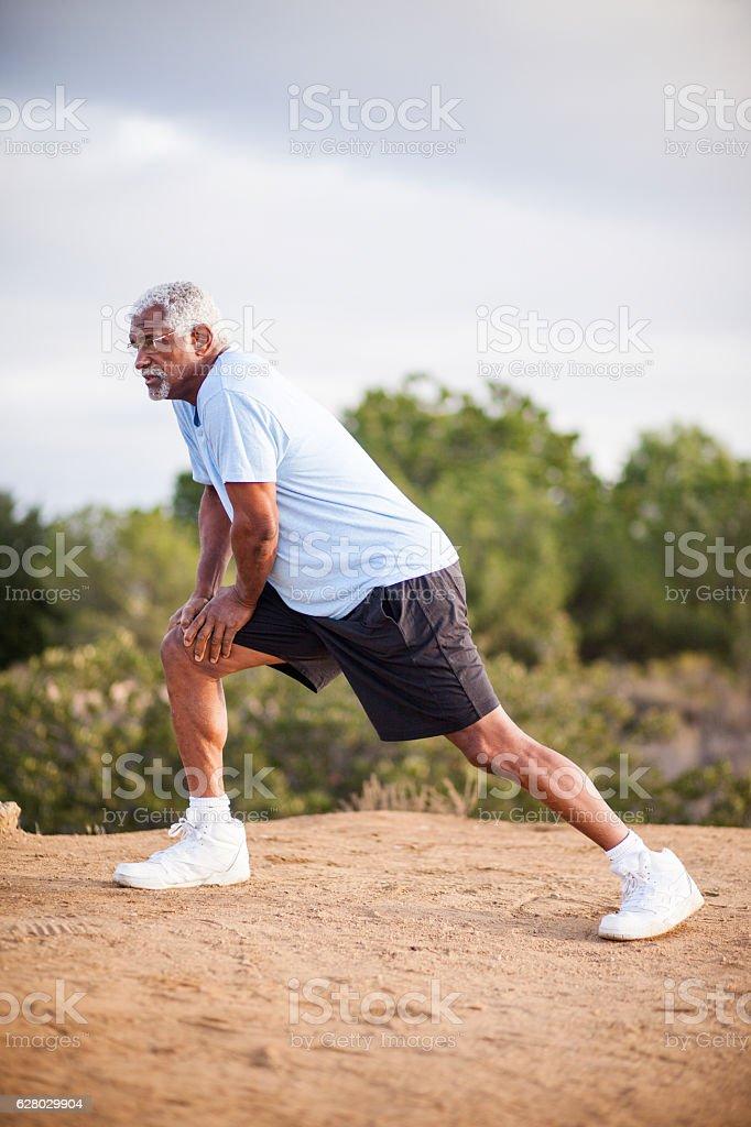 Senior Black Man Stretching and Exercising Outdoors stock photo