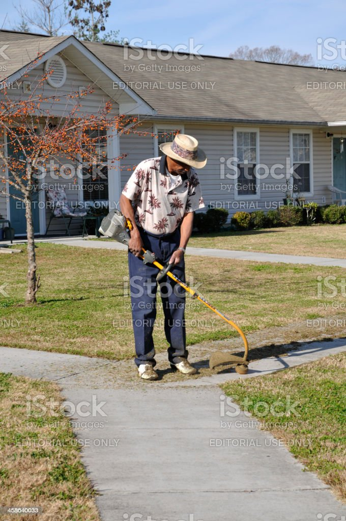 Senior black man uses a weedeater. stock photo