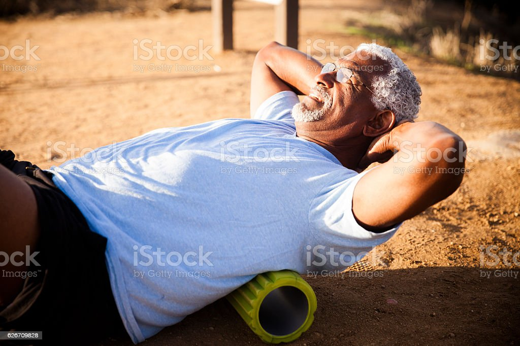 Senior Black Man Using Foam Roller stock photo