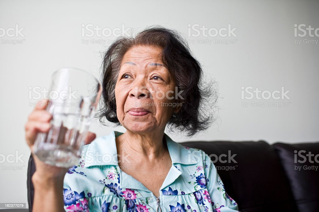 Senior black woman holding a glass of water royalty-free stock photo