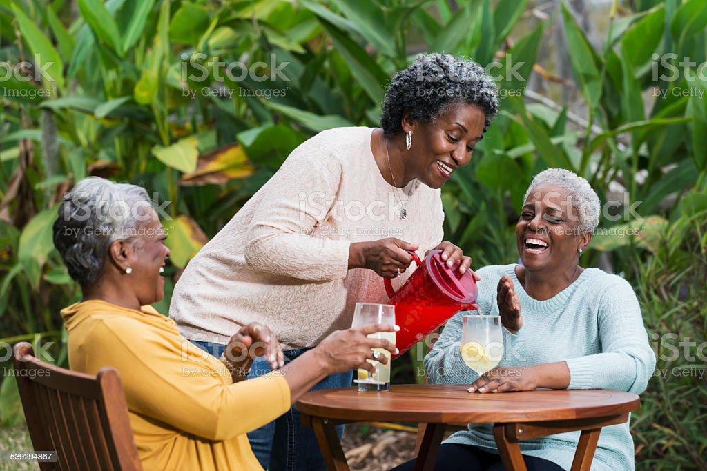 Senior black woman serving lemonade to her friends stock photo