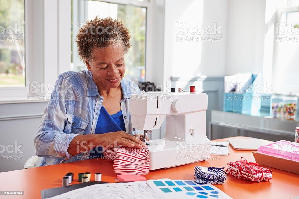 Senior black woman stitching fabric using a sewing machine stock photo