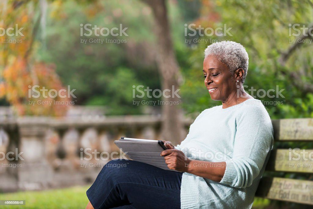 Senior black woman using a digital tablet stock photo