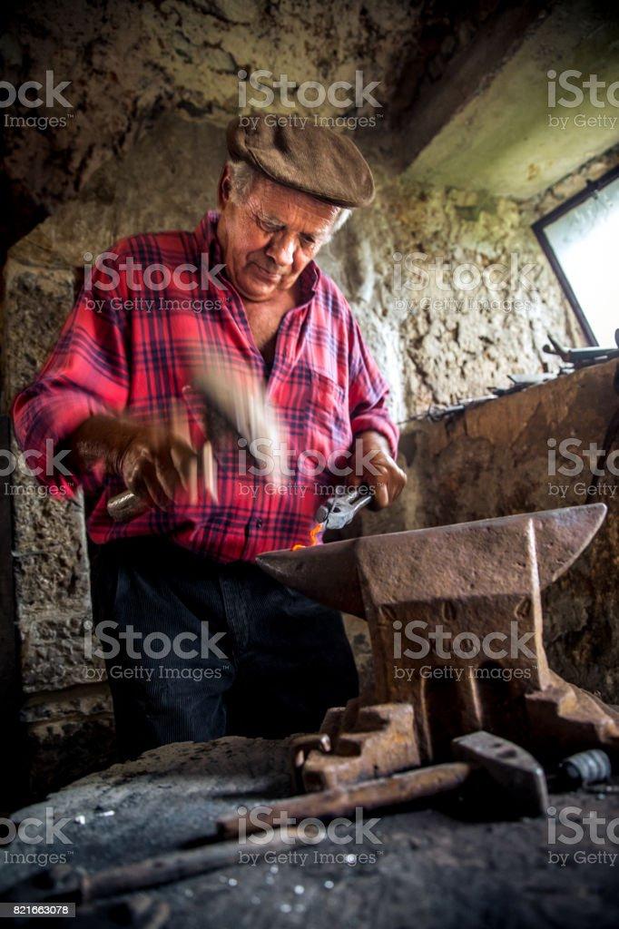 Senior Blacksmith Man Forging an Iron Sickle stock photo