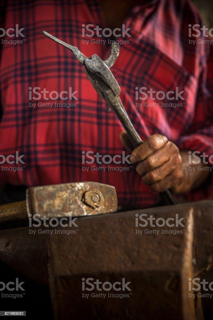 A Senior Blacksmith Man Making a Sickle stock photo