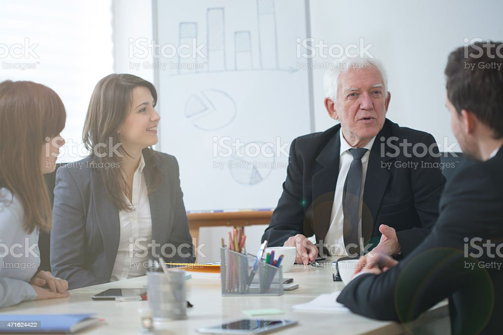 Senior boss and employees during conference stock photo
