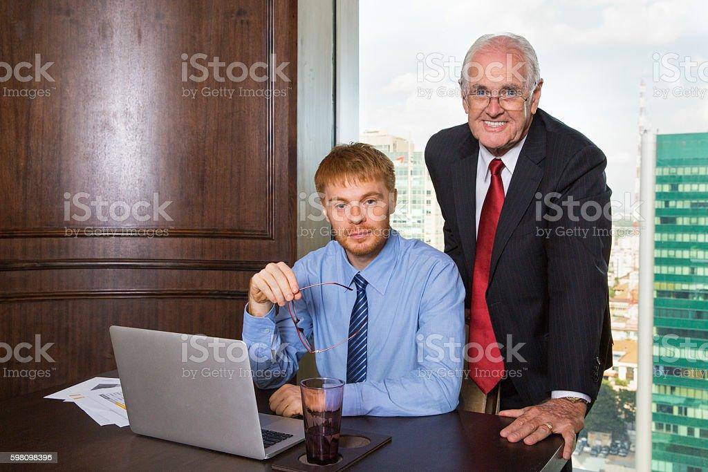 Senior boss and his colleague posing, smiling at camera stock photo