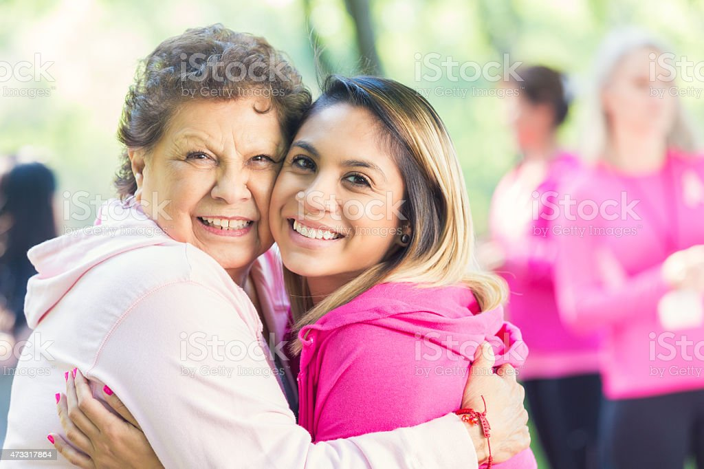 Senior breast cancer survivor with granddaughter at charity race event stock photo
