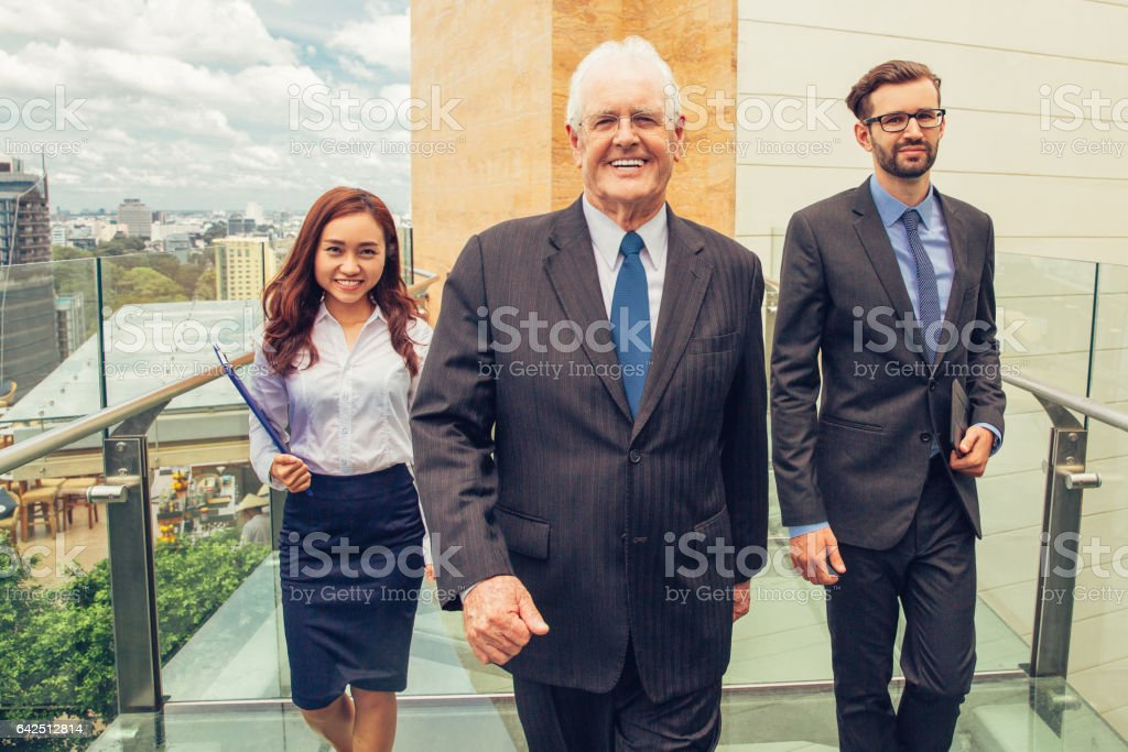 Senior Business Leader with Assistants on Bridge stock photo