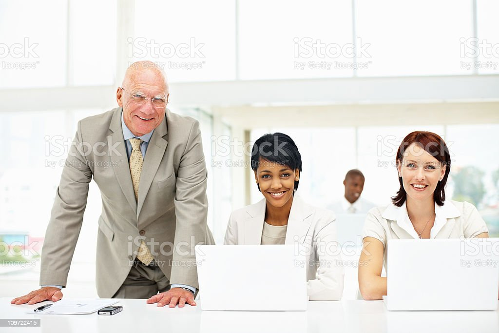 Senior business man and his successful team working on laptop royalty-free stock photo