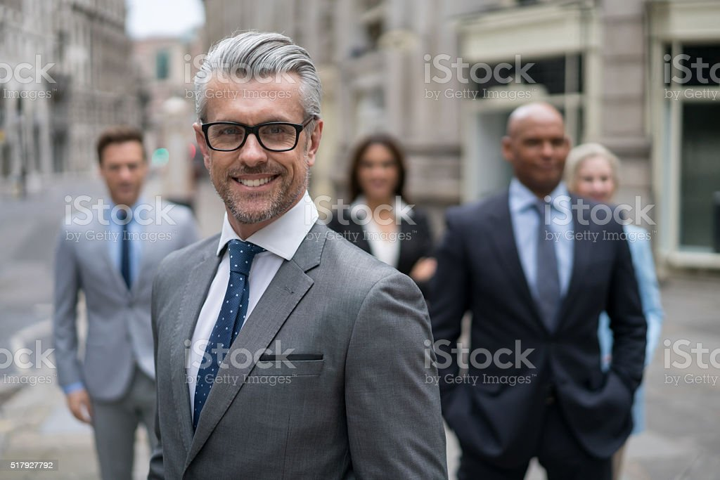 Senior business man leading a group stock photo