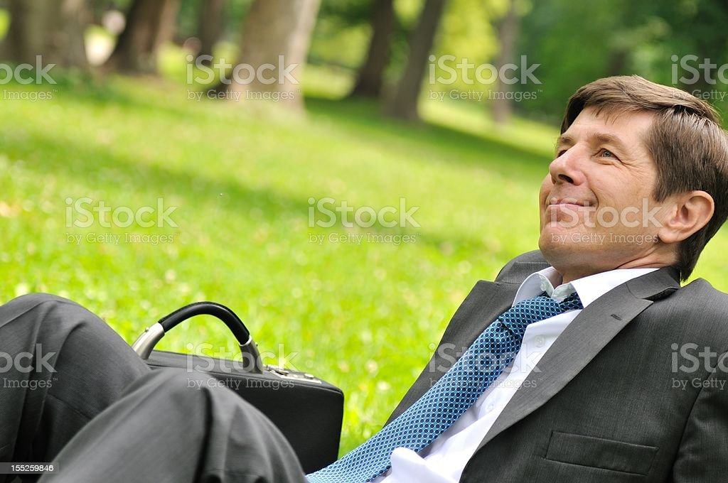 Senior business man siting in grass royalty-free stock photo