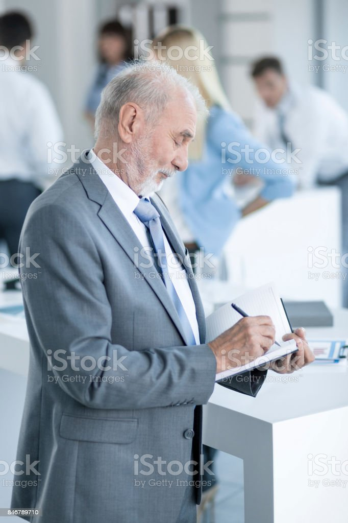 Senior Business Man standing and taking notes in the office stock photo