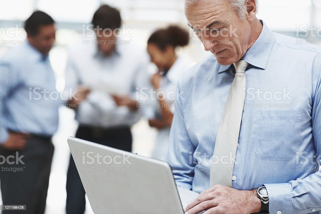 Senior business man using laptop with coworkers at the back royalty-free stock photo