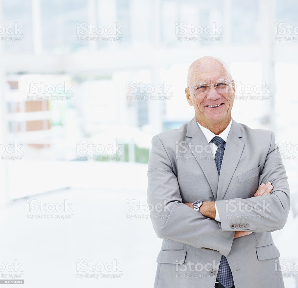 Senior business man with arms crossed smiling at office royalty-free stock photo