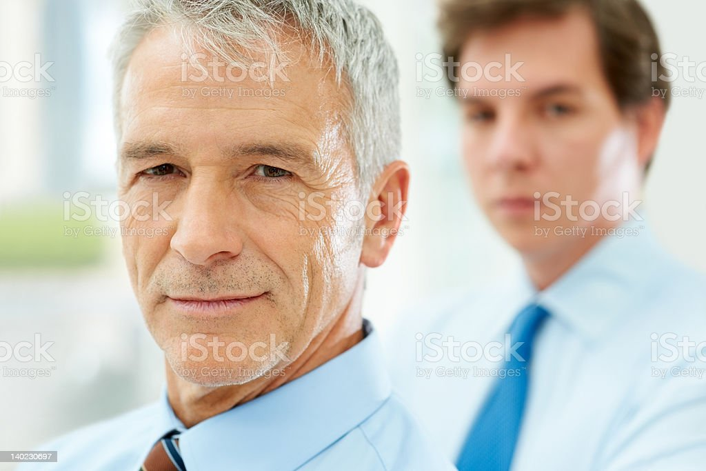 Senior business man with colleague in background stock photo
