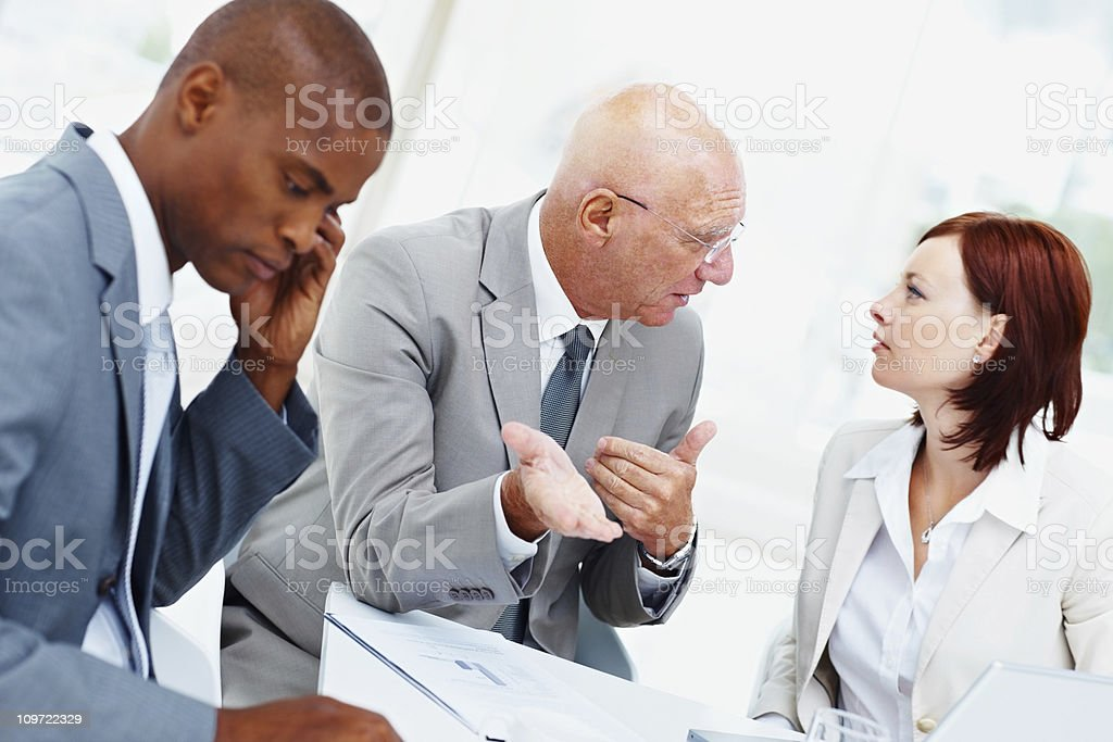 Senior business man with his team discussing in the office royalty-free stock photo