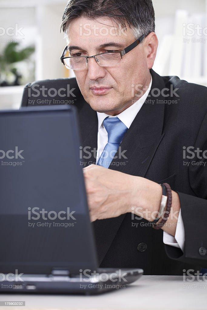 Senior business man working on laptop royalty-free stock photo