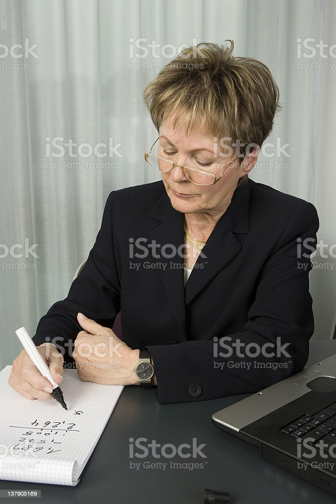 Senior business woman calculating royalty-free stock photo