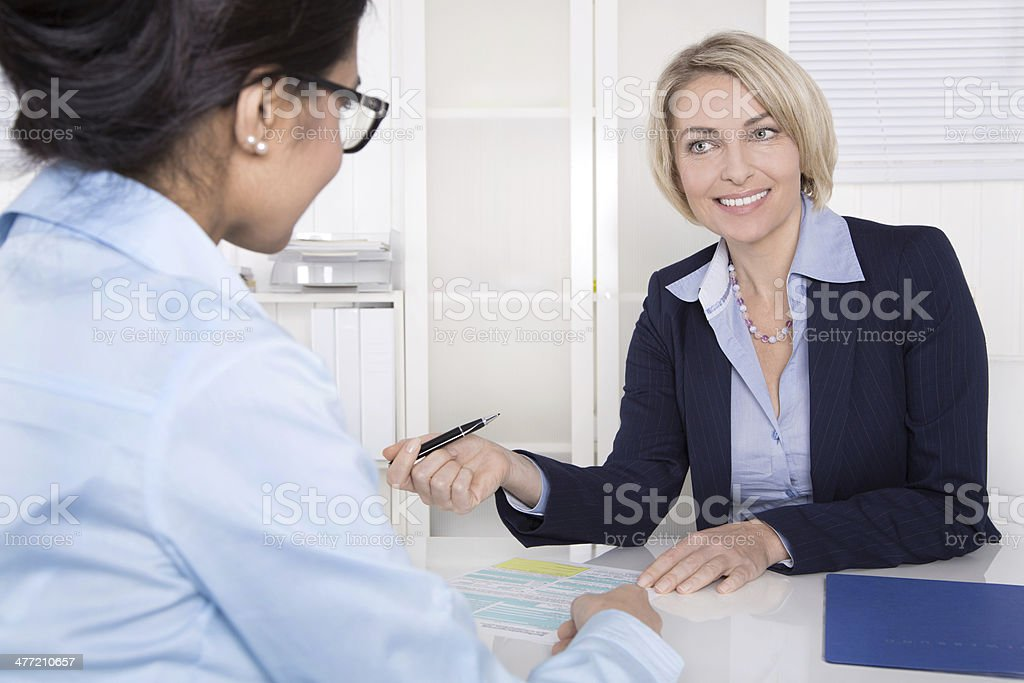 Senior business woman in interview with a trainee - application stock photo