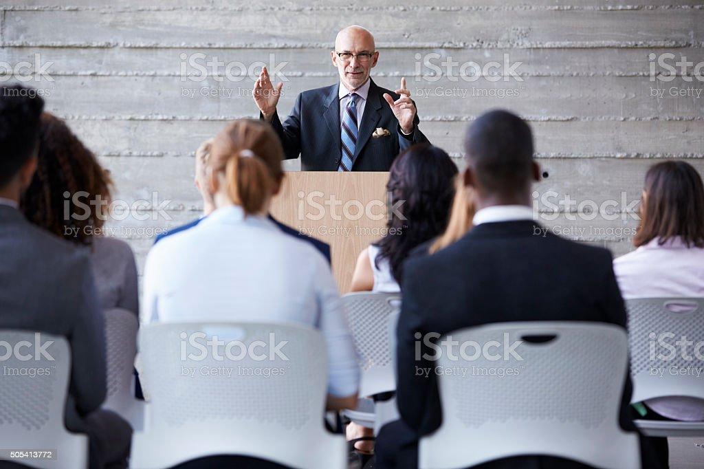 Senior Businessman Addressing Delegates At Conference stock photo