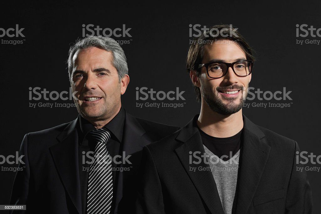 Senior businessman and young businessman smiling standing side by side stock photo