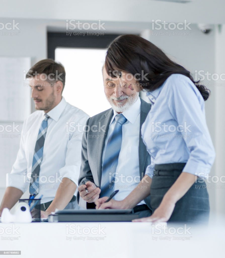 Senior businessman and young businesswoman working together in office stock photo