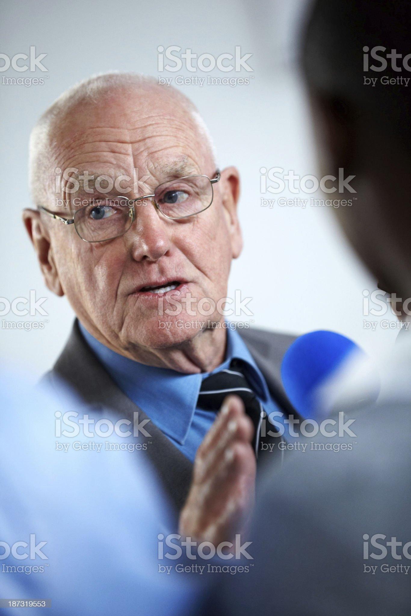 Senior businessman answering media journalist royalty-free stock photo