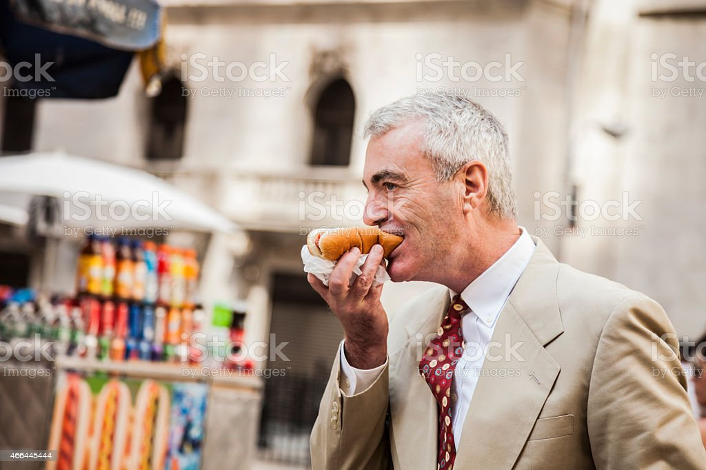 Senior businessman buying an hot dog stock photo
