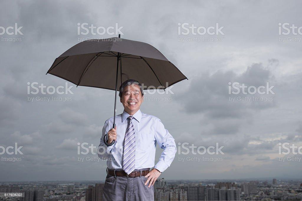 senior  businessman hold an umbrella stock photo