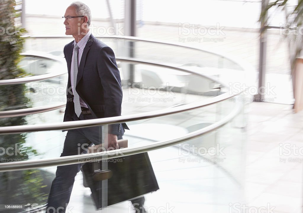 Senior businessman in a hurry with briefcase in lobby royalty-free stock photo