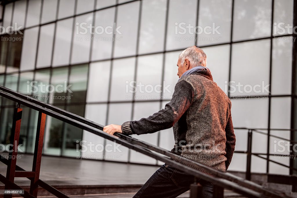 Senior businessman in casual clothing moving up the stairs. stock photo