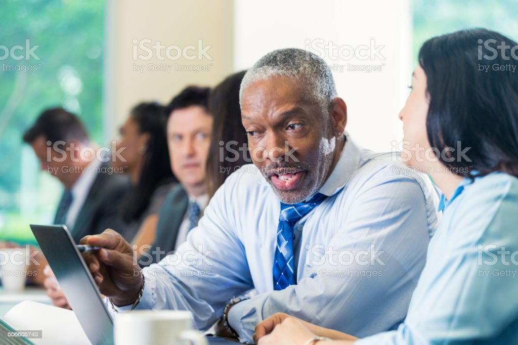 Senior businessman in meeting or conference with professional colleagues stock photo